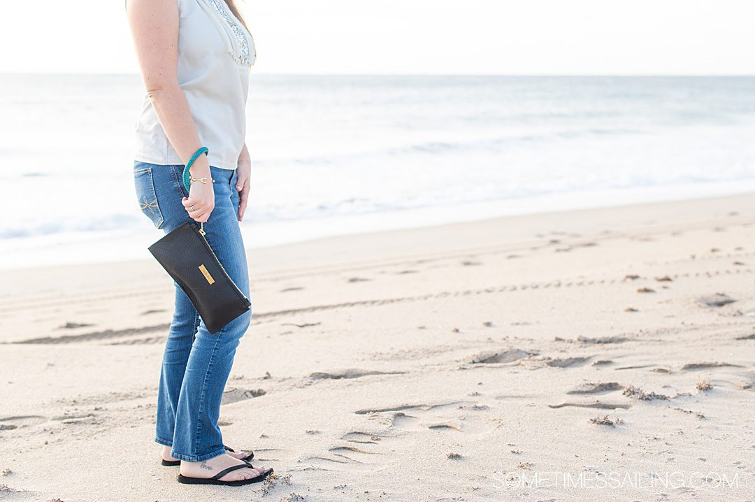 Woman holding a black leather clutch on the beach.