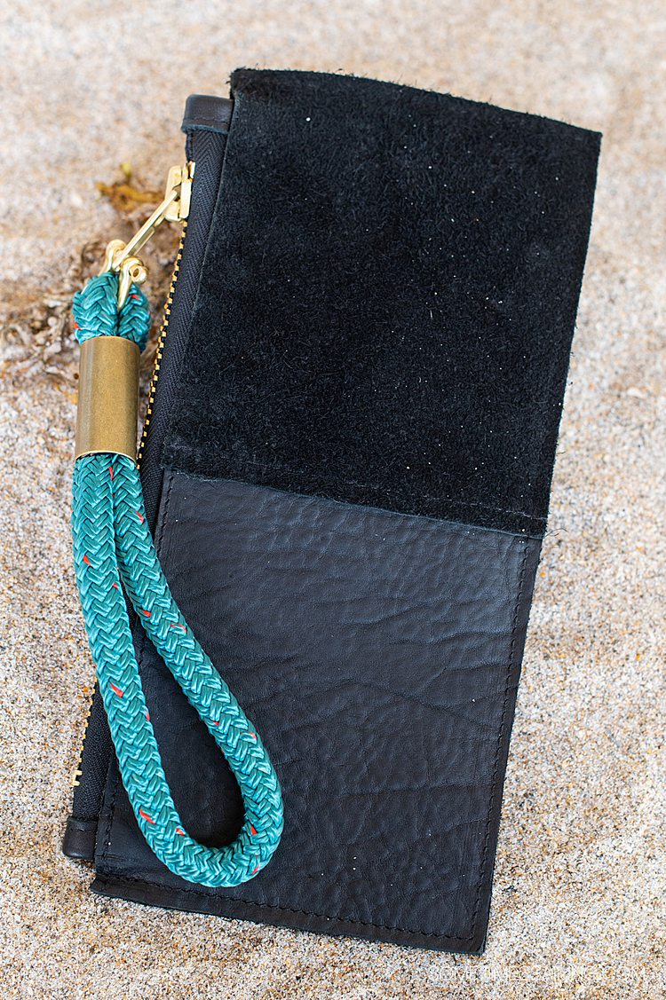 Rectangular black leather clutch in the sand with a teal rope wristlet, from Wildwood Oyster Co.