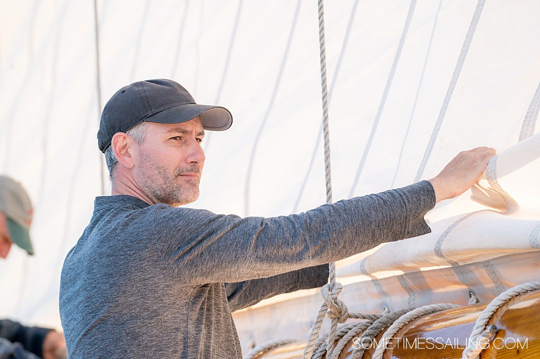 Man folding the sails on a Maine Windjammer Cruise sailing experience.