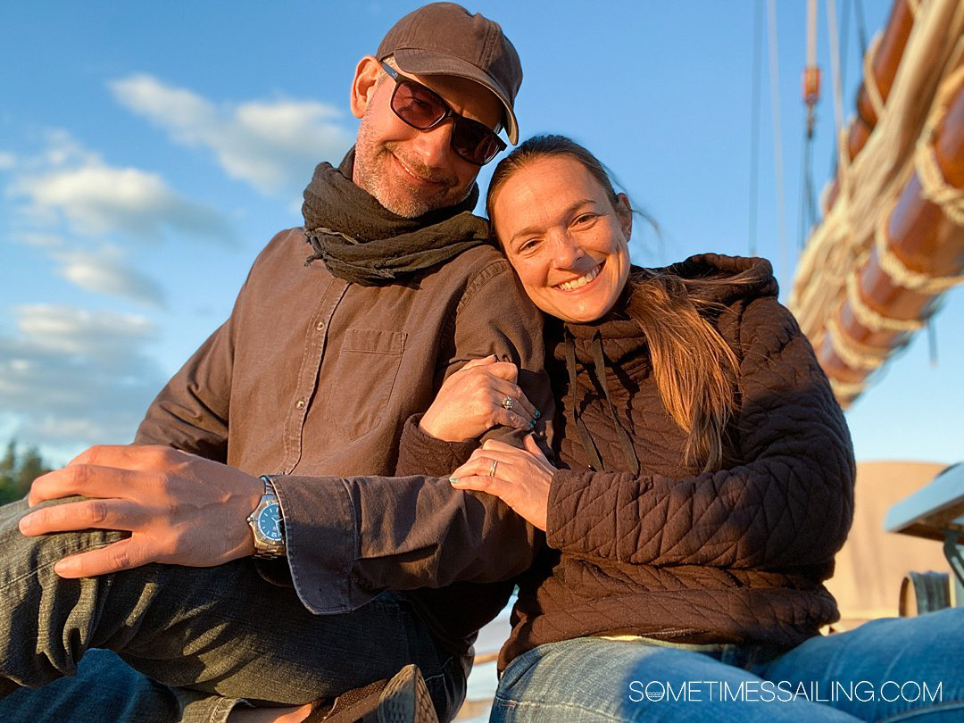 Man and woman with golden light on their faces wearing layers of dark colored clothing on a Maine Windjammer cruise ship.