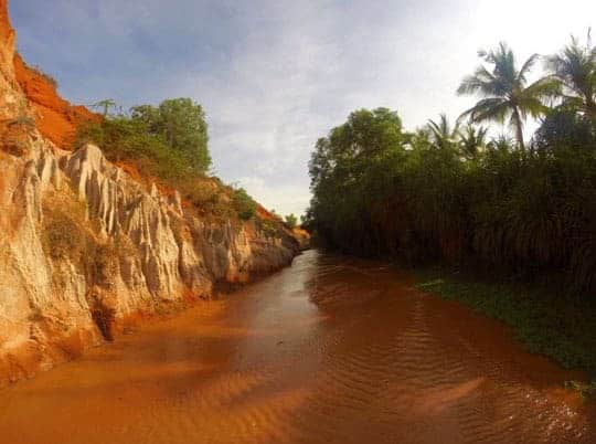 A brown water stream runs between white and red cliffs on the left and luscious jungle green on the right at Fairy Spring (Suoi Tien)