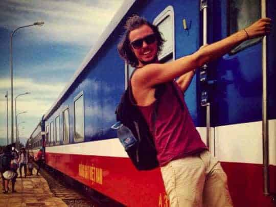 A Western backpacker holds onto a train in Vietnam!