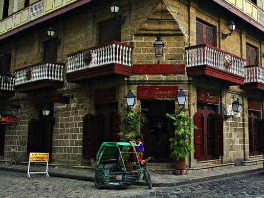 A boy stands next to his tuk tuk in front of a beautiful colonial building on a corner in Manila