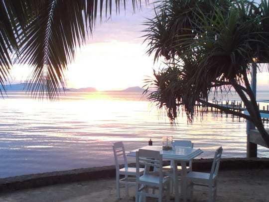 A Table At Kep Sailing Club With The Sun Setting in the Background