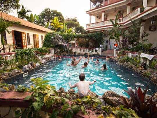 Backpackers play volleyball in the pool at Phong Nha Farmstay