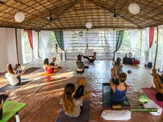 A Room of People in Boat Pose During A Yoga Teacher Training Course at Parimukti