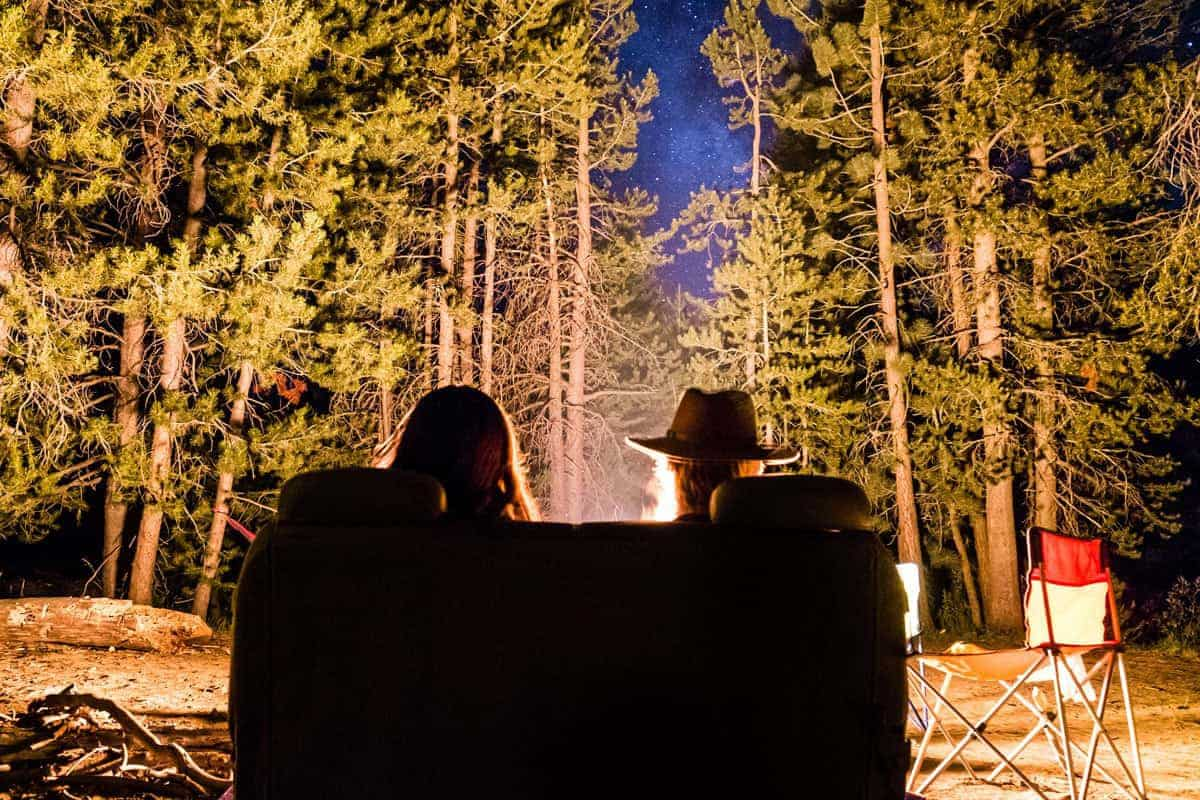 The Silhouette of a Couple Sitting on a Sofa in a Forest, Representing Luxury Camping
