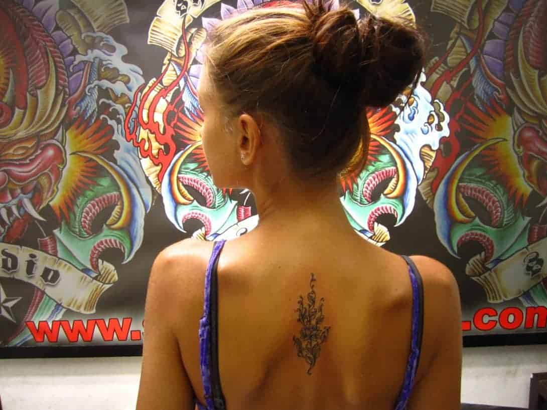 A girl poses in a tattoo shop with her new tat