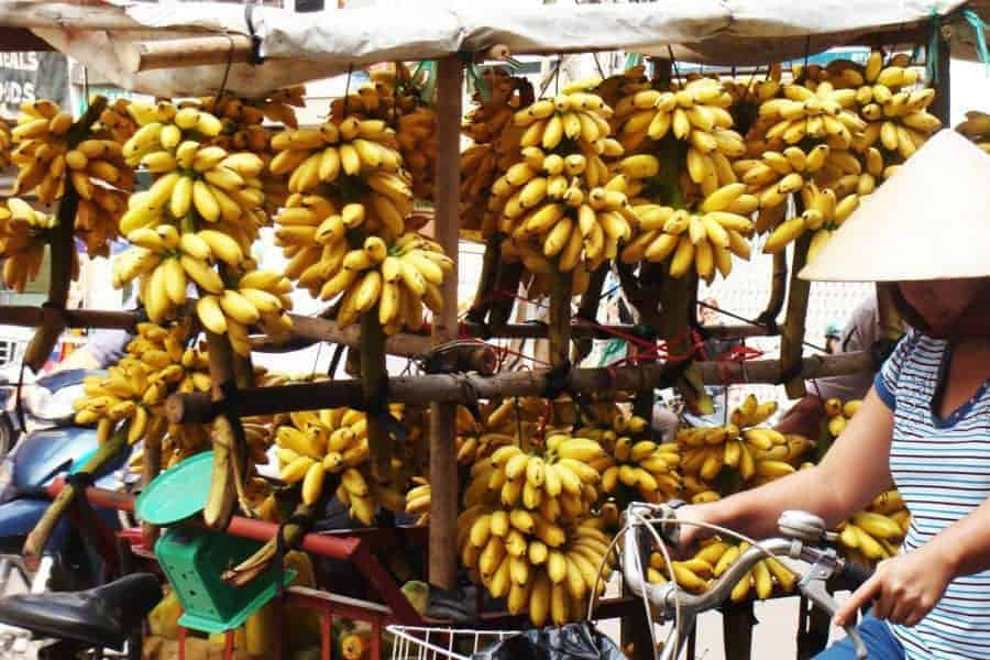 A woman on a bike passes a banana stall in Ho Chi Minh City, Vietnam