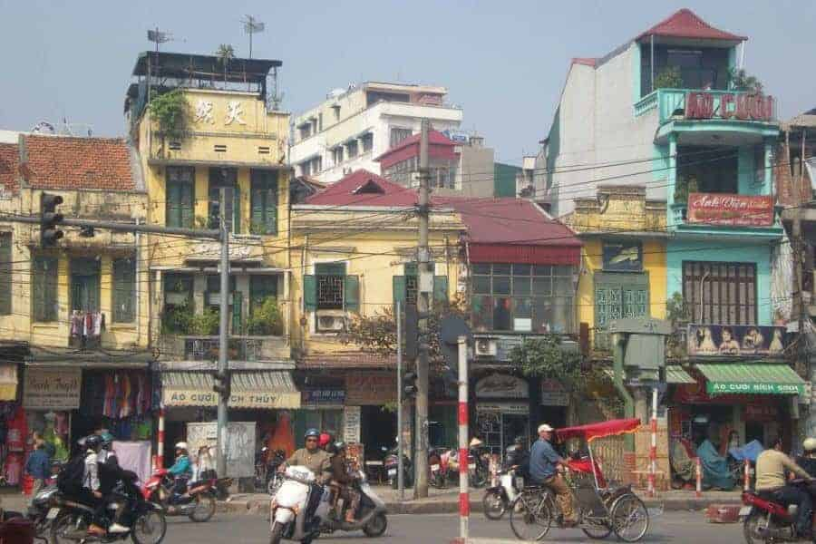A busy street scene showing mopeds, buildings and many electrical cables in Hanoi