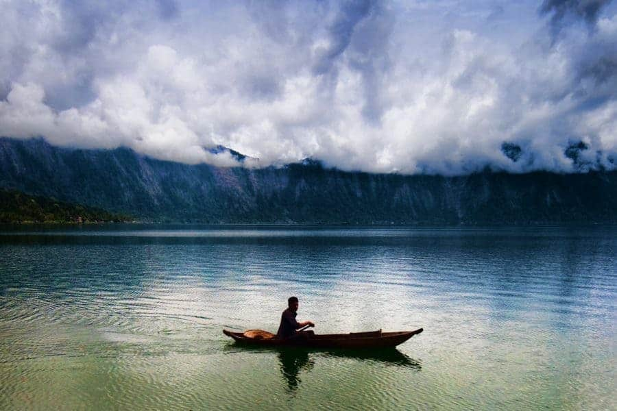 A fisherman in a boat on Lake Toba, photo by Flash Parker