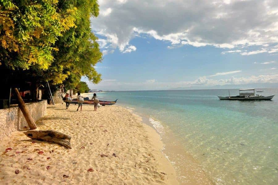 A beach with trees, a couple of people and a boat in Moalboal