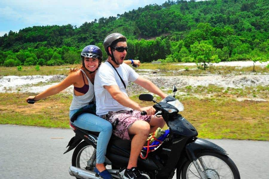 A young couple motorbiking in Southeast Asia.
