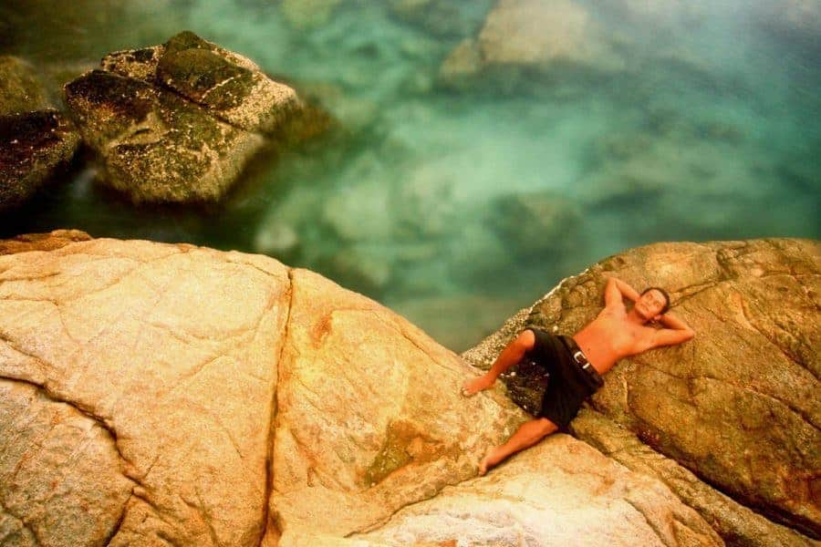 A man sunbathes on a rock on The Perhentian Islands.