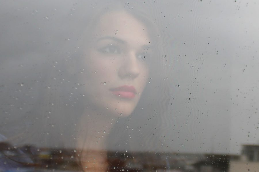A Girl Gazes Sadly Through A Window With Drops Of Rain On It