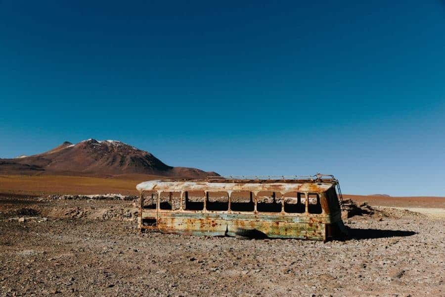 The Shell of an Abandoned Bus in a Desert