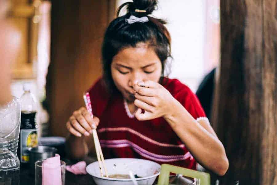 A young girl eating with chopsticks.