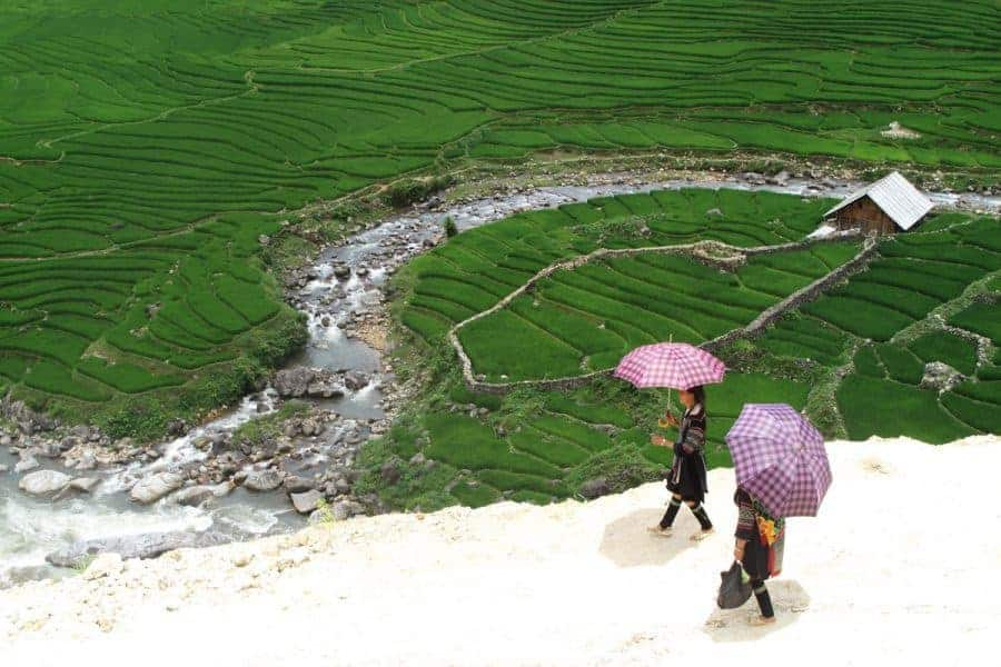 Two girls with umbrellas look over a valley in Sapa, Vietnam