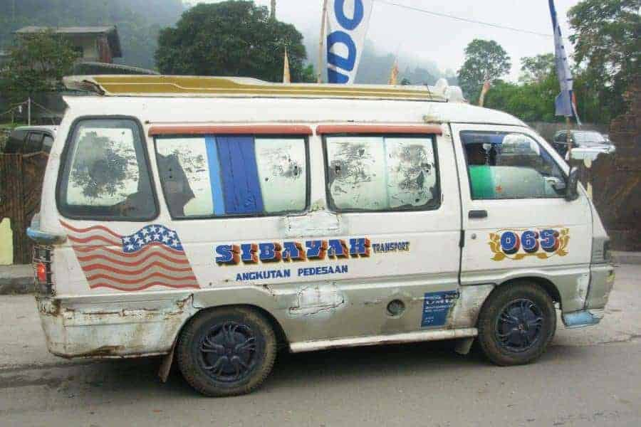 Blue and white mini van in bad condition functioning as a bus in Sumatra, Indonesia - Cheapest Place in Southeast Asia