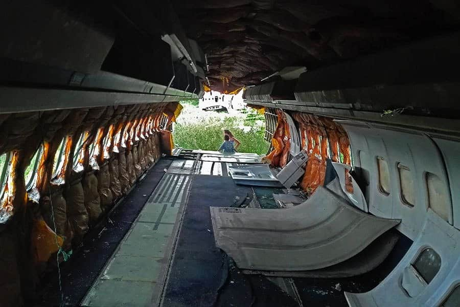 Looking-out-from-the-inside-of-an-abandoned-MD-82-with-local-boy-talking-to-Nikki-at-Bangkok's-aeroplane-graveyard,-Thailand