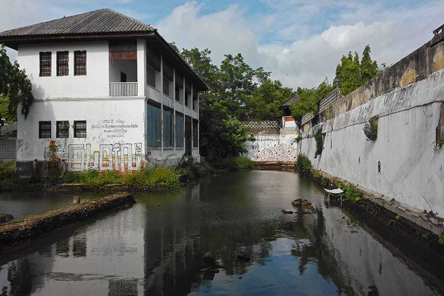 A-cell-block-seen-across-the-moat-water-at-the-abandoned-women's-prison,-Chiang-Mai,-Thailand