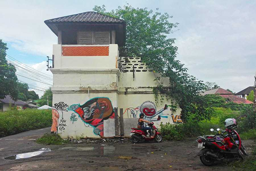 Nikki-Scott-sits-on-a-bike-in-front-of-a-watchtower-and-next-to-the-way-in-to-the-abandoned-women's-prison,-Chiang-Mai