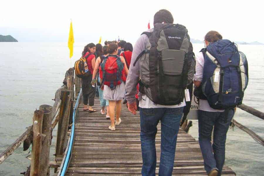 A group of backpackers walk on a wooden pier. None of them has a wheeled backpack