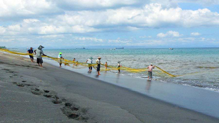 Fishermen pull in their nets in Lombok, Indonesia