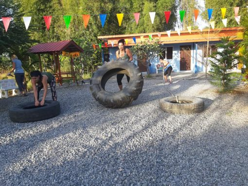 A Woman Trains With a Big Tyre at Battle Conquer Muay Thai