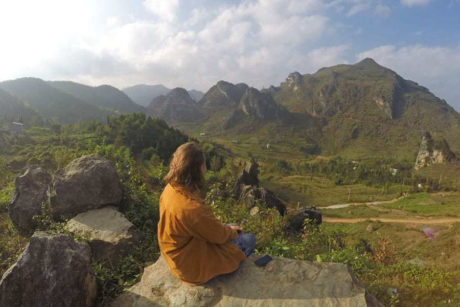 The author sits on a rock looking over a valley