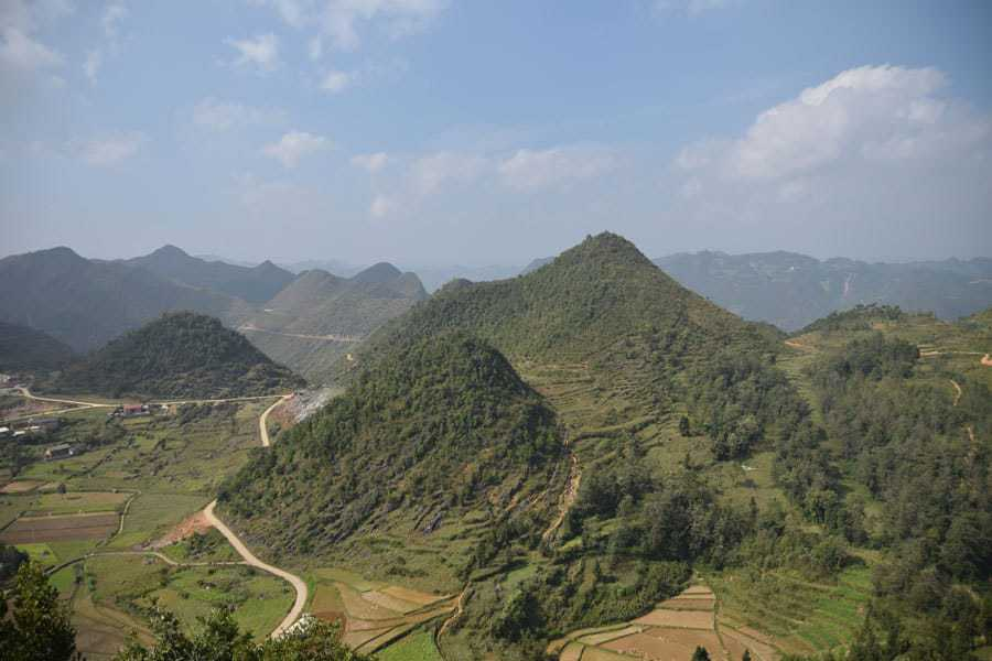 The road winds round the mountains of the Ha Giang loop on a sunny day