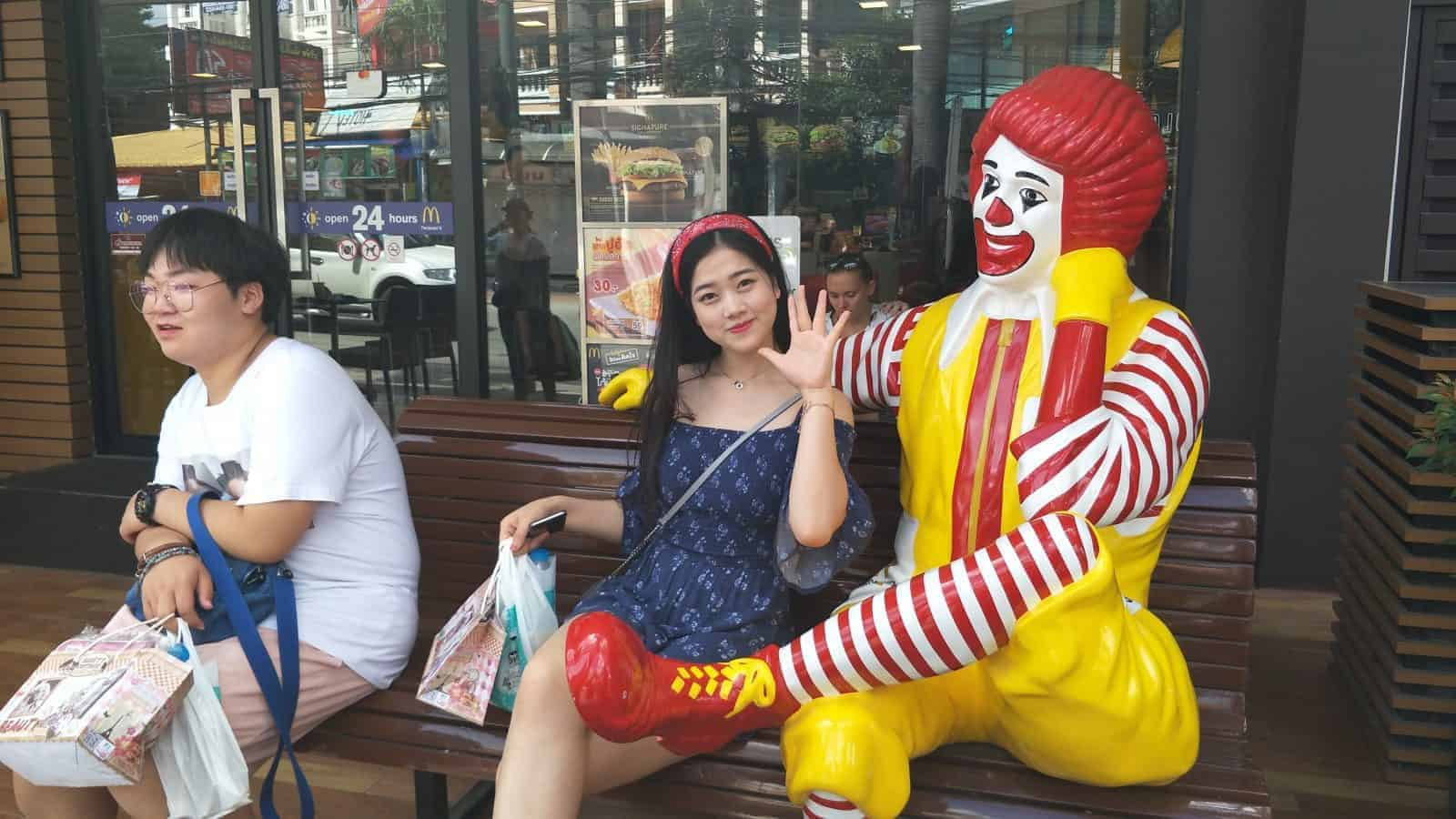 A Chinese Tourist poses with Ronald McDonald in Chiang Mai.