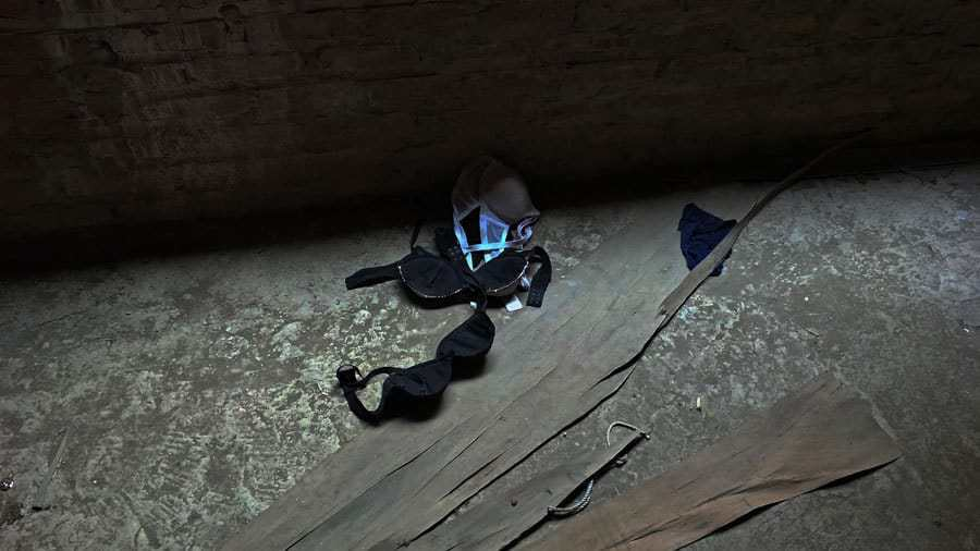 Several bras on the floor of an abandoned building.