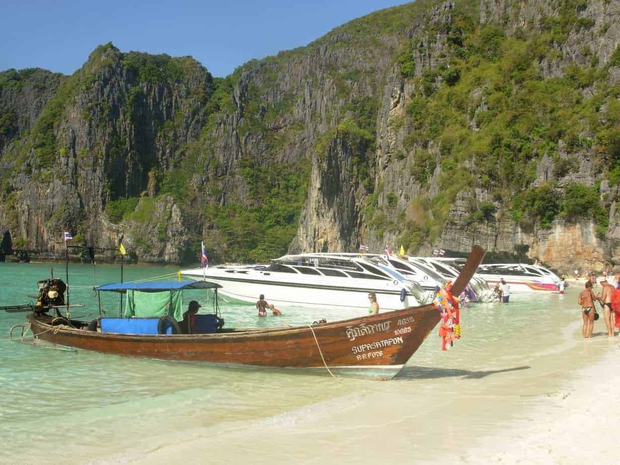 Longtail and speedboats moored on the beach at Maya Bay.