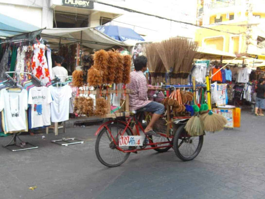 """A local man """"pedals"""" brushes down the Khao San Road."""