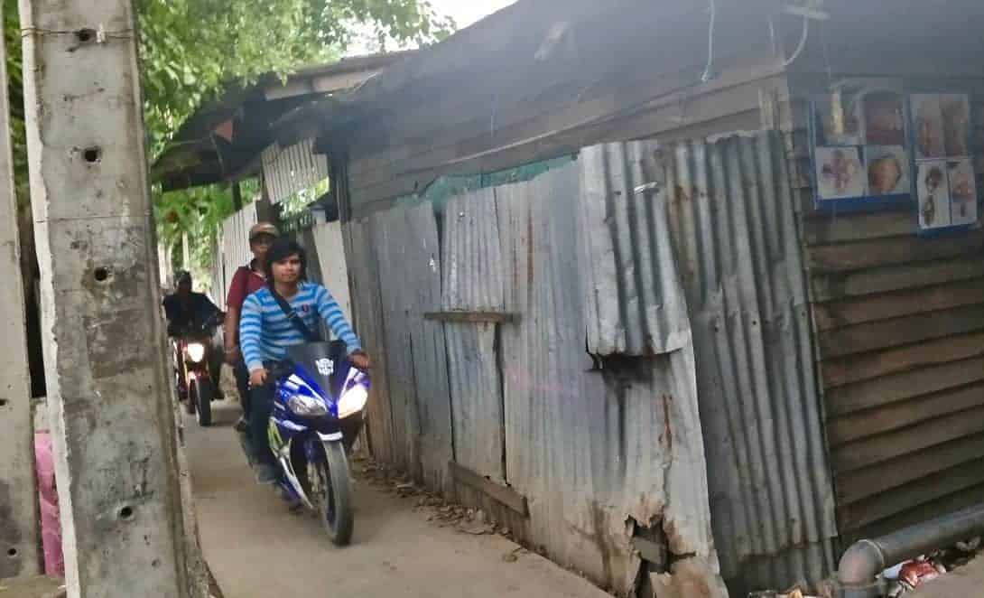 Corrugated iron houses and a Thai man on a motorbike.