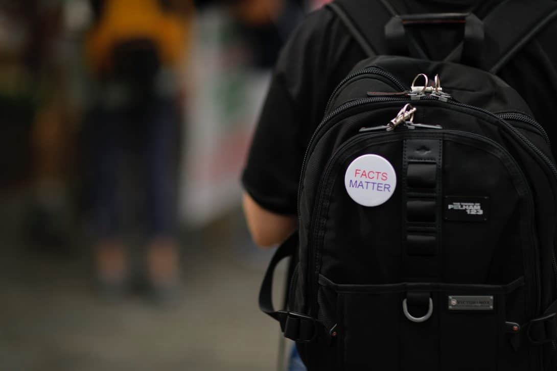 Guy wears a travel daypack with a badge saying 'facts matter'.