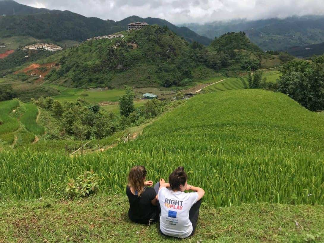 Two Girls Sit on The Floor, Looking Across The Valley During Their Sapa Trek