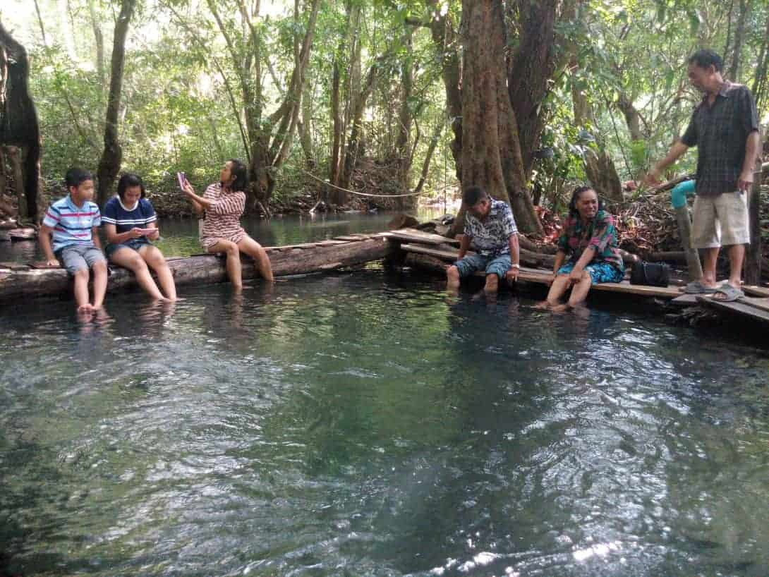 A group of Thai people have their feet cleaned in the natural fish spa in Khanom