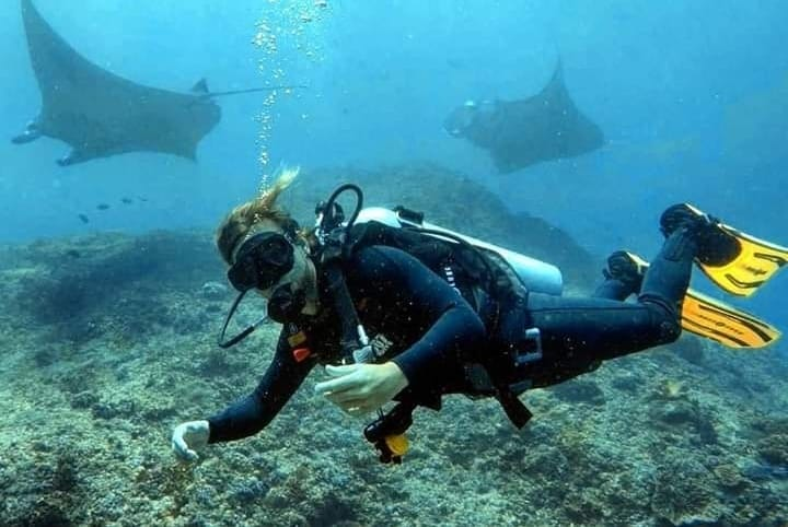 A Diver in Nusa Lembongan Indonesia with Manta Rays in the Background.