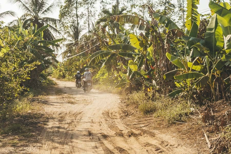 Scooters drive down a dusty road