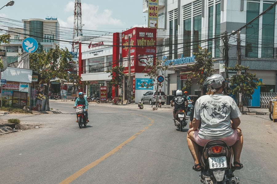 A Group Of Travellers Travel Through a Town in Vietnam on Motorbikes