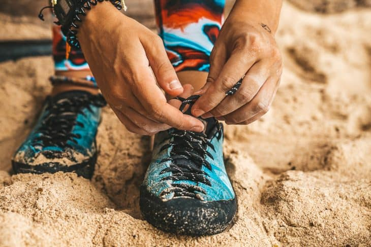 Person ties shoelace on rock climbing shoes