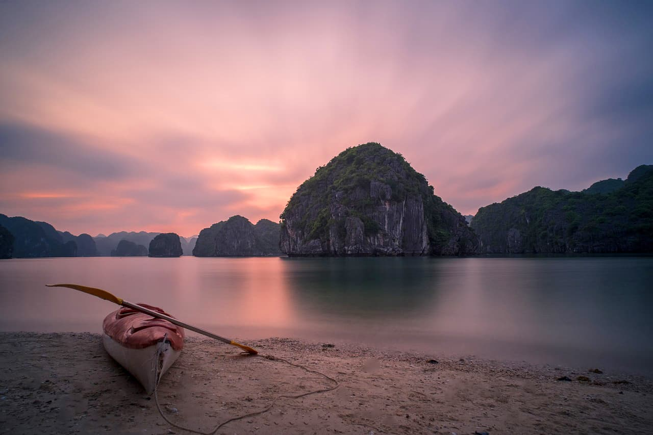 The sun sets of Lan Ha Bay with a Kayak in the foreground.
