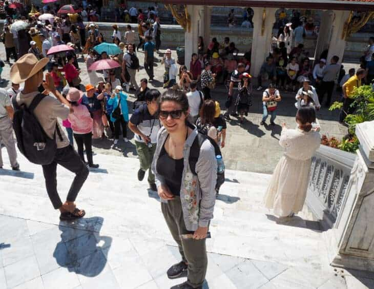 Girl stands amongst crowds at Grand Palace