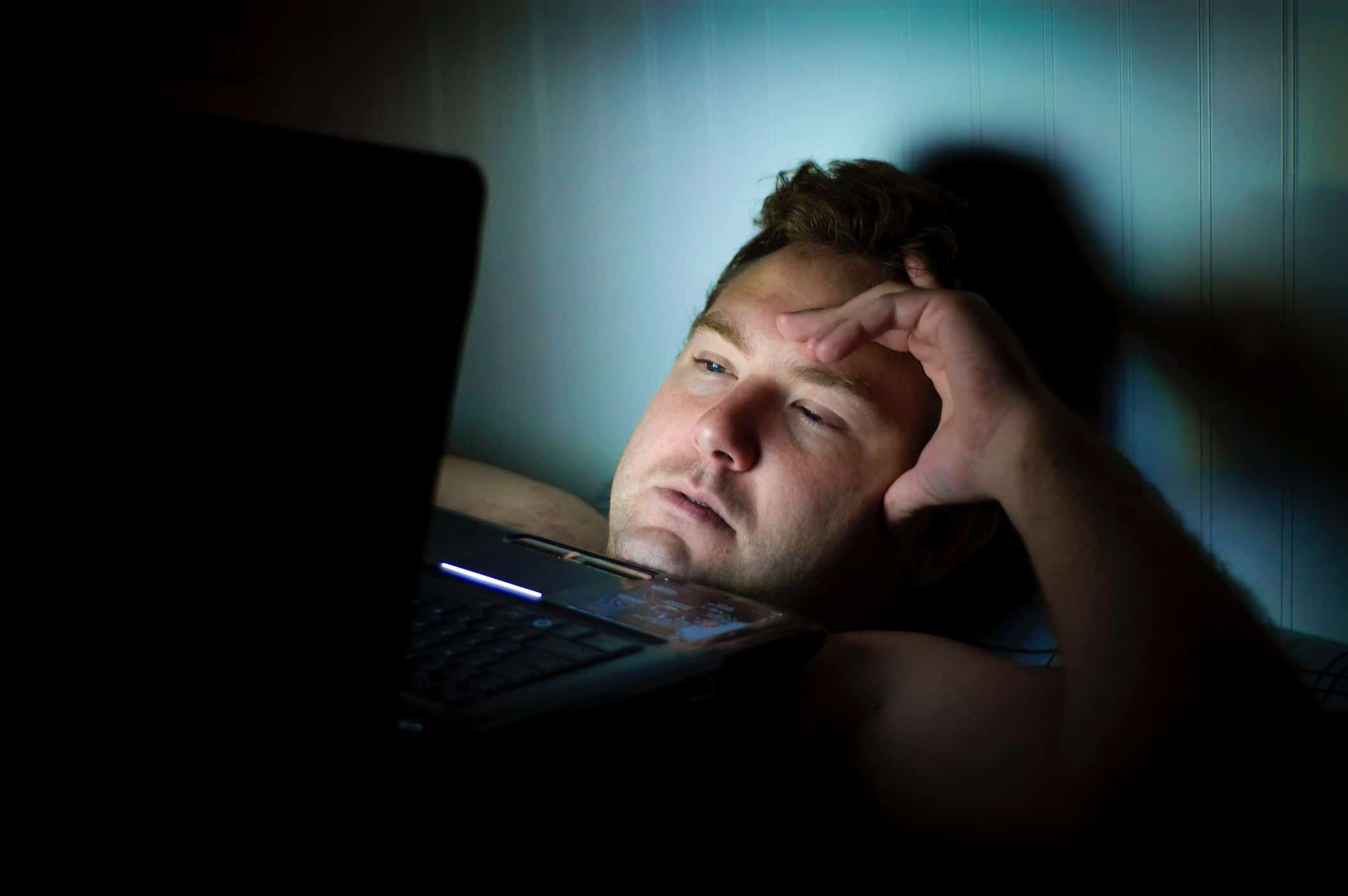 Man looking at computer screen worrying about travel insurance.
