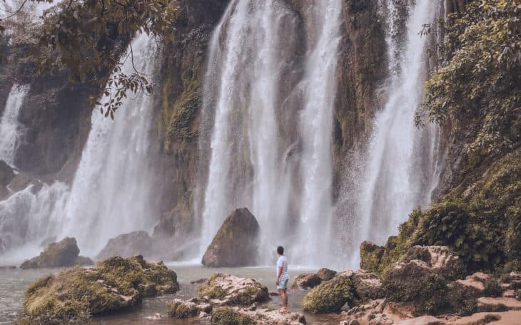 Man stands next to Ban Gioc Waterfall.