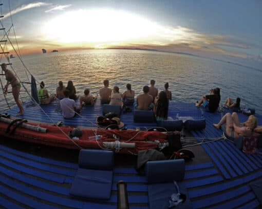 Backpackers watch sunset from junk boat.
