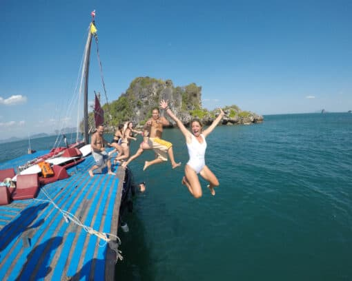 Backpackers jumping off boat