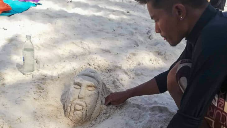 Man makes face in the sand.